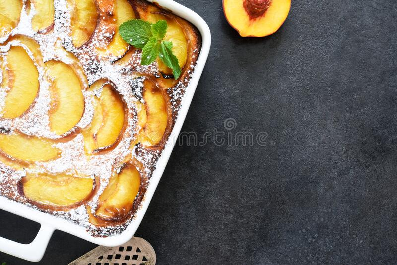 Delicate cake with peaches sprinkled with powdered sugar on a black concrete background stock images