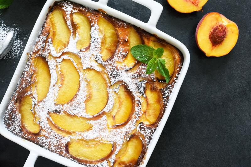 Delicate cake with peaches sprinkled with powdered sugar on a black concrete background stock image