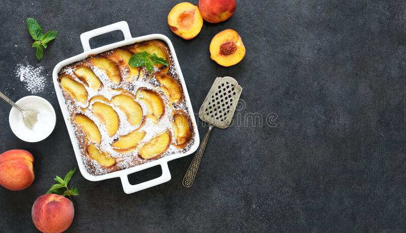 Delicate cake with peaches sprinkled with powdered sugar on a black concrete background royalty free stock image