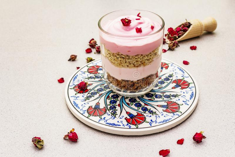 Delicate cream dessert. Traditional turkish edible rose, flower petals. Painted ceramics with a national pattern, stone concrete background, copy space, close stock photos