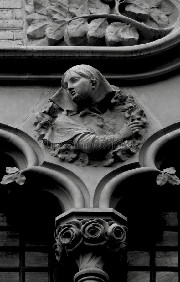 Delicate female figure surrounded by nature. Shot in black and white detail on the sculpture on the facade of this historic building representing some characters royalty free stock images