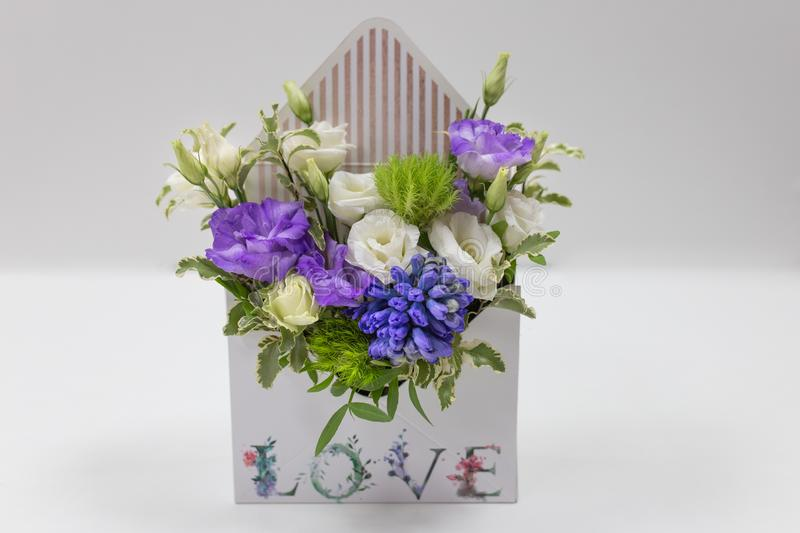 Delicate floral arrangement gift of fresh flowers in a box in the form of an envelope with the inscription Love, on a light back. Ground. eustoma, leaves. Colors stock photo