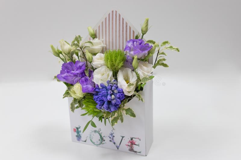Delicate floral arrangement gift of fresh flowers in a box in the form of an envelope with the inscription Love, on a light back. Ground. eustoma, leaves. Colors stock photography