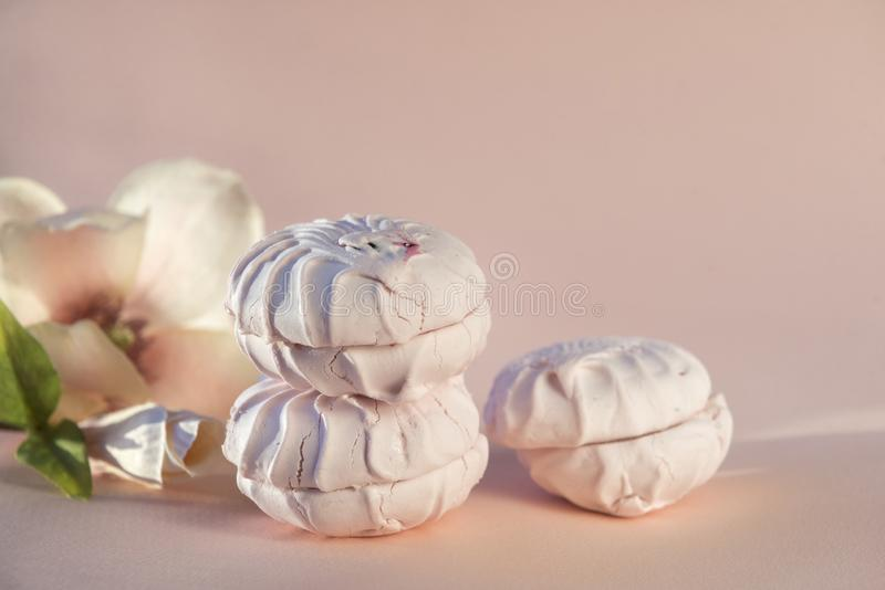 Delicate fruit marshmallow, Magnolia flower on beige background, delicate dessert stock photos