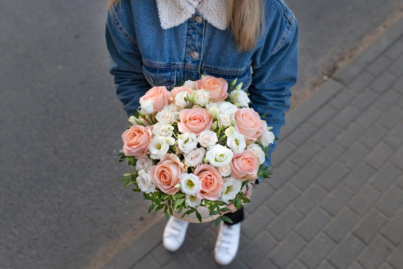 Delicate impressive bouquet of white and pink roses in a hat box. In the hands of a young girl in an open space stock images