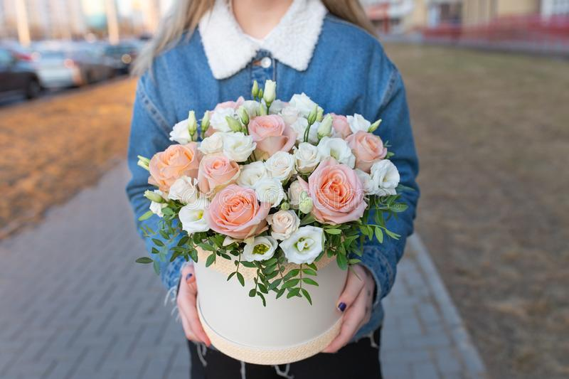 Delicate impressive bouquet of white and pink roses in a hat box. In the hands of a young girl in an open space stock photo