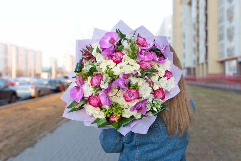 Delicate impressive bouquet of white and pink roses in a hat box. In the hands of a young girl in an open space royalty free stock photography