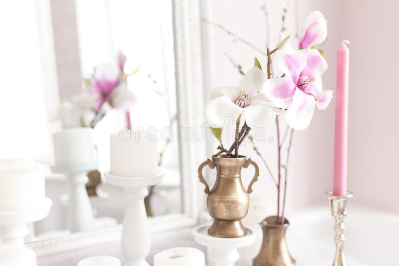 Delicate and light decoration of the dressing table with flowers, candles. Soft focus. Close up. royalty free stock images