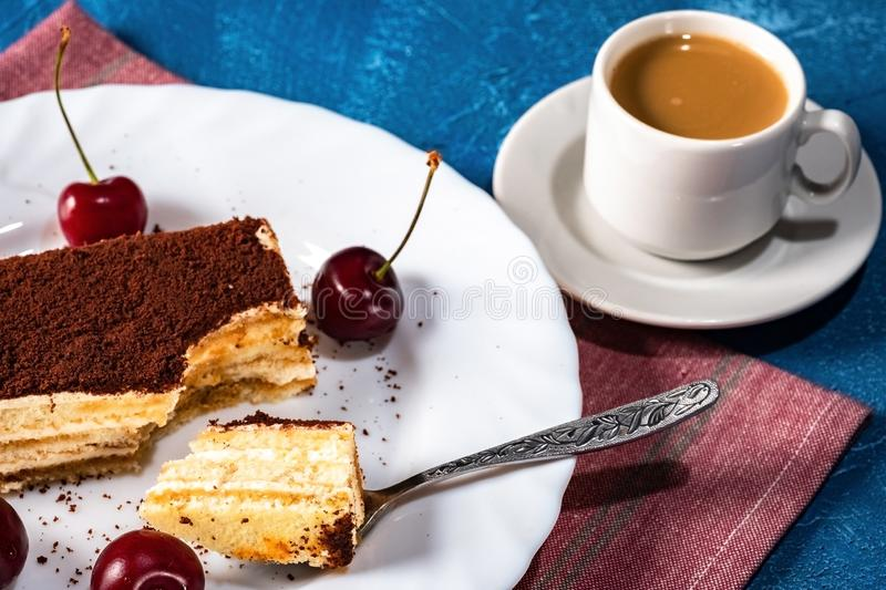 Delicate, light tiramisu cake and a Cup of hot coffee with milk stock photos