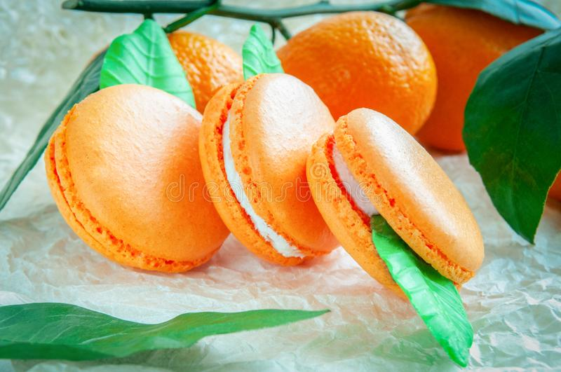 Delicate macaroons with mandarin. On white craft paper. Blurred background.  royalty free stock photos