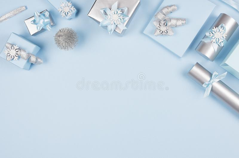 Delicate pastel blue christmas background - various gift boxes with glitter ribbons and bows, small christmas tree as decorative. Delicate pastel blue christmas stock photography