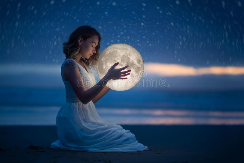 Delicate photography, Astrology, Women`s magic. Beautiful attractive girl on a night beach with sand and stars hugs the moon, art royalty free stock photography