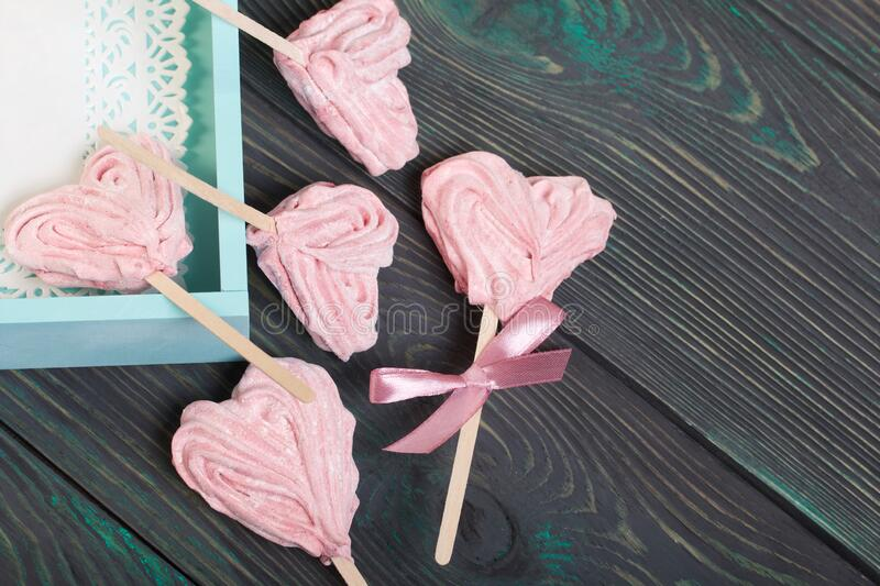 Delicate pink marshmallows in the shape of a heart on a stick. One with a ribbon tied to a bow. Near the turquoise color tray. Lies on brushed pine boards stock image