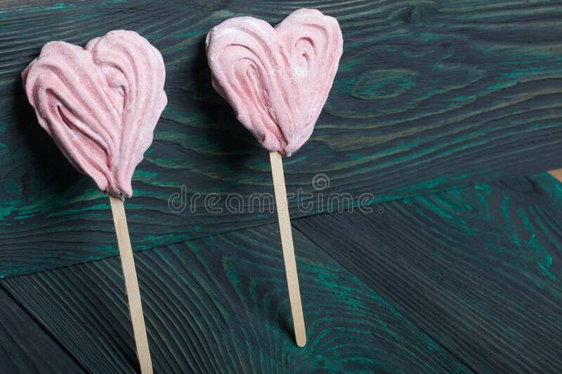 Delicate pink marshmallows in the shape of a heart on a stick. Several pieces lie on brushed pine boards painted in black and. Green stock photos