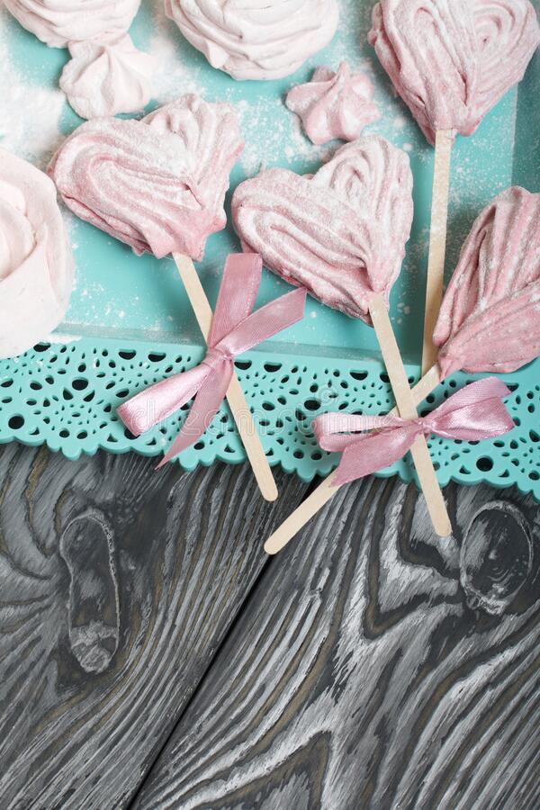 Delicate pink marshmallows in the shape of a heart on a stick. Some with a ribbon tied to a bow. Lies on a turquoise tray. Against. The background of brushed royalty free stock images