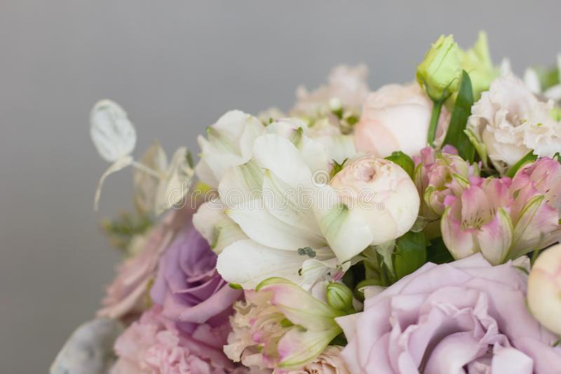 The delicate rustic floral bouquet of rose lilac on grey background. The delicate rustic floral bouquet of purple rose lilac on grey background royalty free stock photos