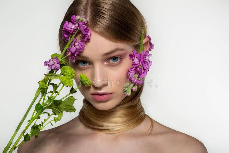 Delicate spring beauty portrait of a beautiful girl with neck wrapped in her hair, purple flowers near her face and stock photos