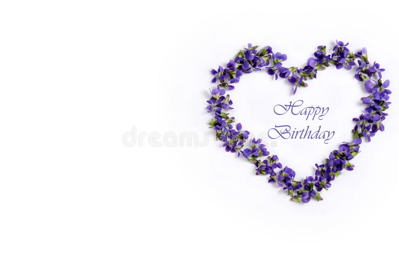 Delicate spring violets in the shape of a heart on a white background. Happy birthday. Happy birthday greeting card. Spring violets in the shape of a heart on a stock photos