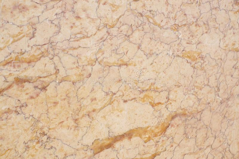 The delicate surface of a yellow natural stone with red stripes is called Crema Valencia stock photography