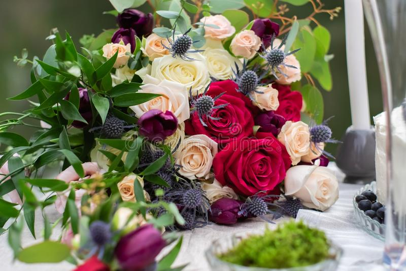 Delicate wedding bouquet with burgundy cream pink roses and feverweed, closeup royalty free stock image