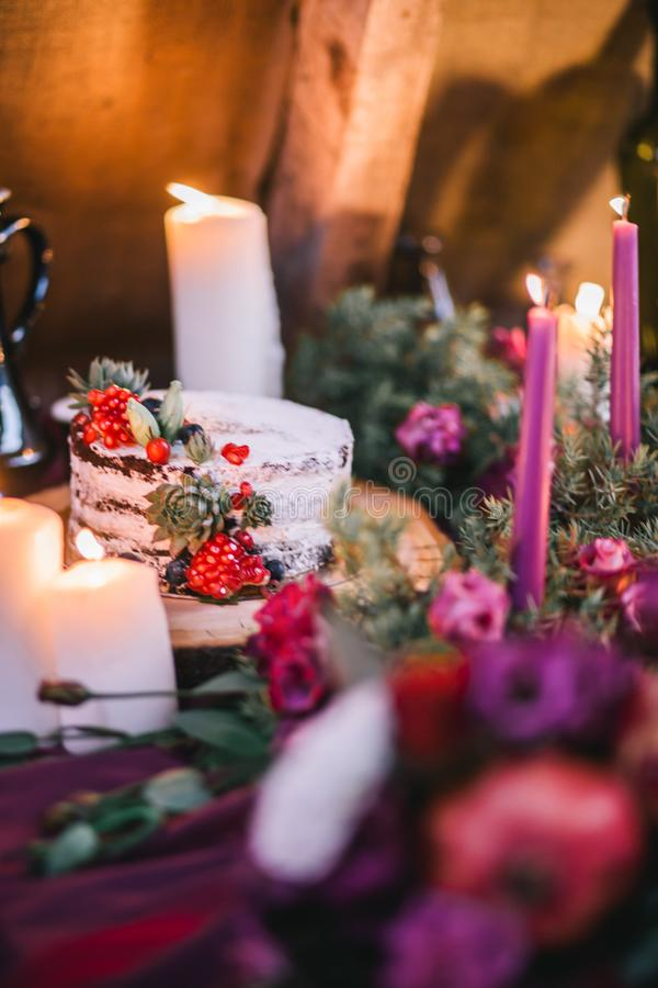 Delicate wedding white cake decorated with pomegranate and succulent surrounded by flowers and candles stock image