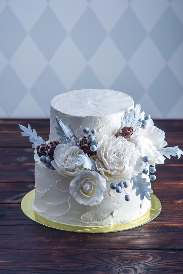 Delicate white bunk wedding cake decorated with an original design using mastic roses. Concept of festive desserts. Delicate white bunk wedding cake decorated stock image