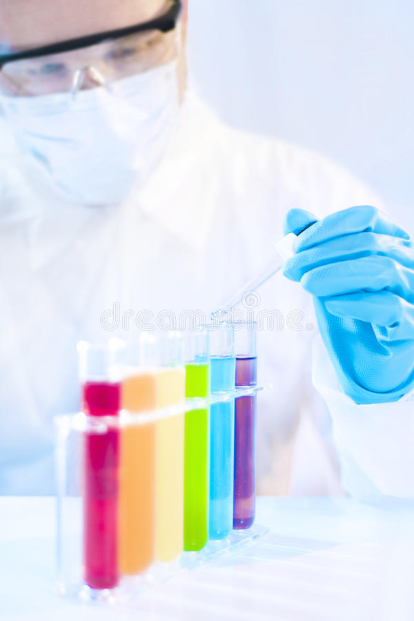 Delicate Work. Man in Protective Suit Picking Drop with Pipette royalty free stock photography