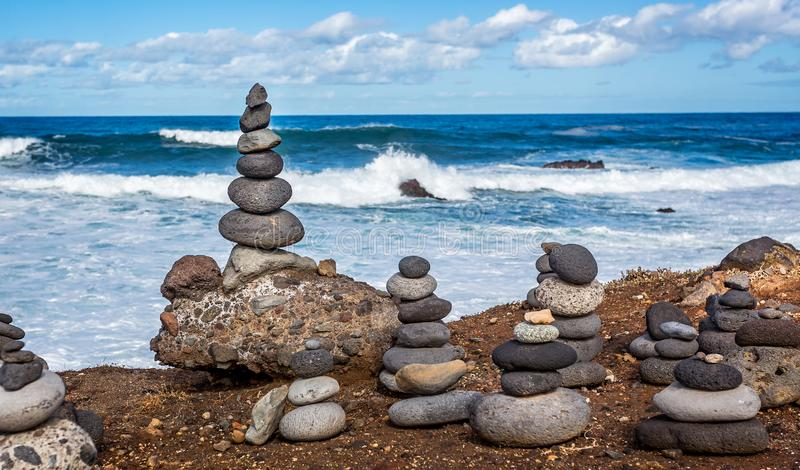 Delicately balanced man made stacks or piles of stones with crashing waves stock photography