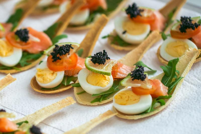 Delicates, appetizer filling with red fish, quail egg, black caviar and lime. Catering service. stock photography