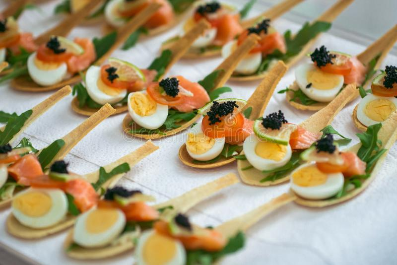 Delicates, appetizer filling with red fish, quail egg, black caviar and lime. Catering service. royalty free stock image