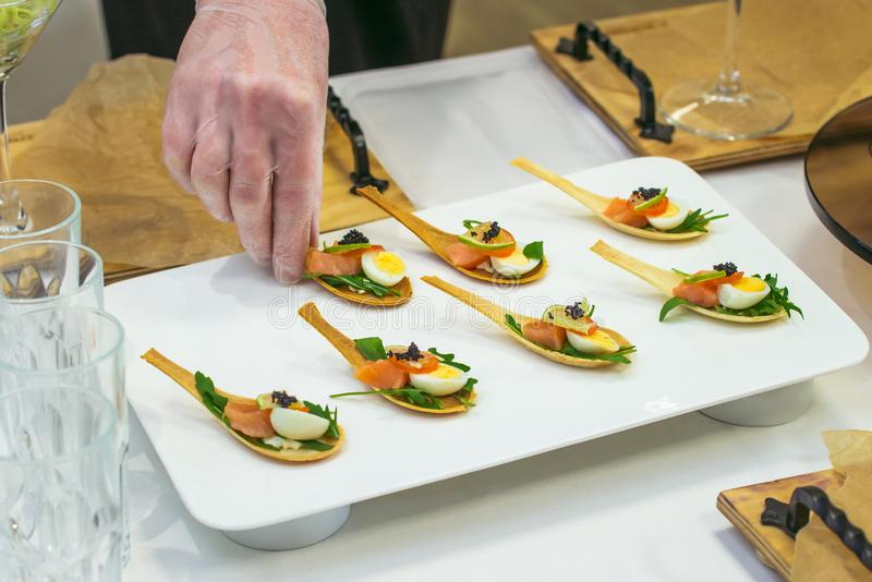 Delicates, appetizer filling with red fish, quail egg, black caviar and lime. Catering service during table decoration. stock photography