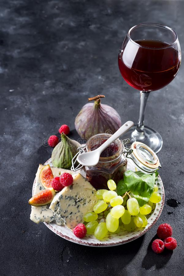 Delicatesse schimmelkazen, fruit en jam in kruik met rode wijn in glas op de zwarte achtergrond van de leisteen, exemplaarruimte stock foto