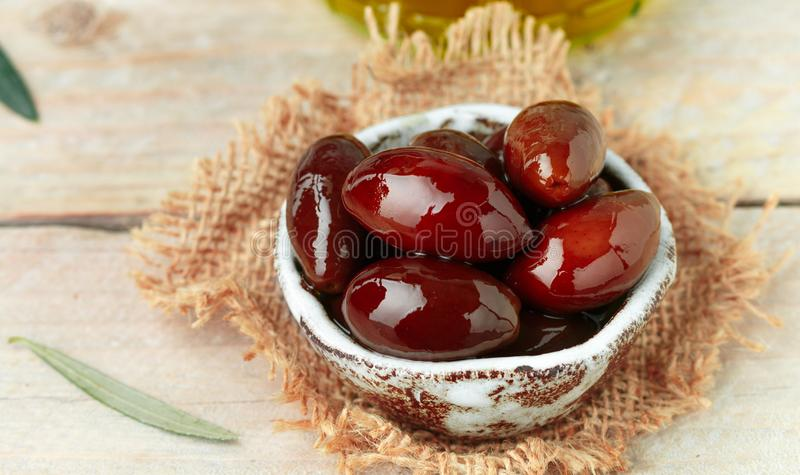 Delicatessen Greek Kalamata black red glossy olives in ceramic bowl. On wooden table close up.  Oil and twigs. Selective focus royalty free stock image