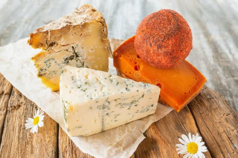 Delicatessen kruidige kazen van verschillende verscheidenheden Rode cheddar, Dor-blauw, Stilton, Belper-heuveltje op mooie geweve stock foto's