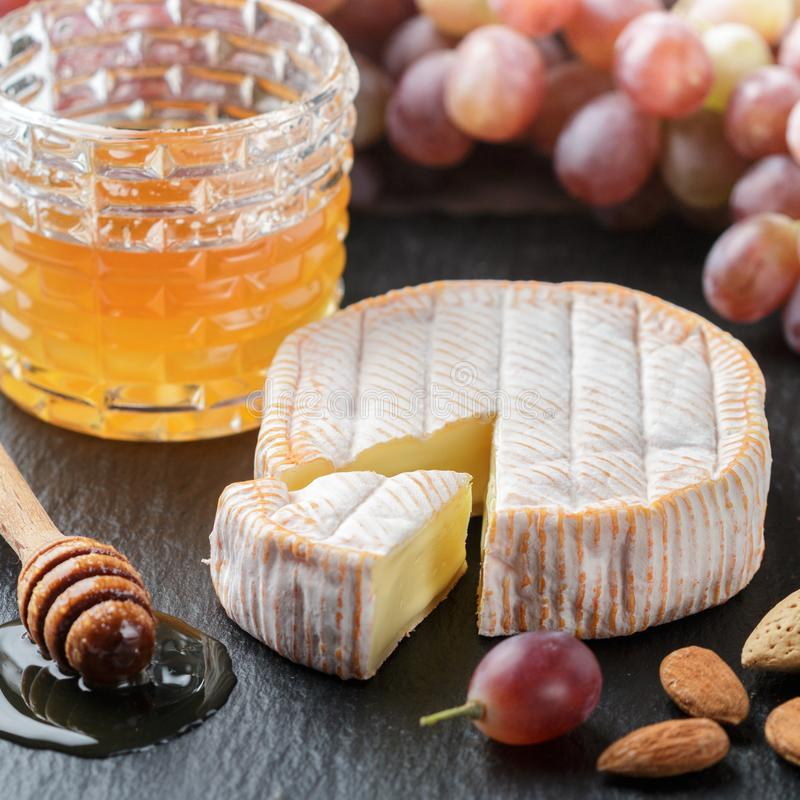 Delicatessen zachte geurige kaas met vorm, honing, amandelen en rode druiven royalty-vrije stock fotografie