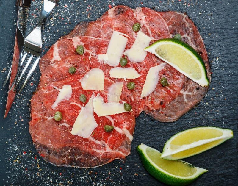 Delicatessenvoorgerecht van vers vlees - rundvleescarpaccio royalty-vrije stock afbeeldingen