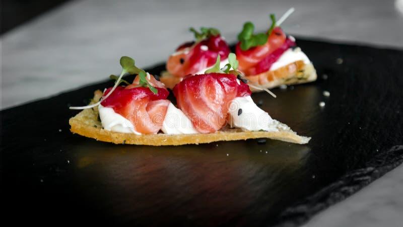 Delicioso divirta o aperitivo do bouche, salmões curados com beterrabas, queijo e a flor alaranjada - alimentos luxuosos foto de stock