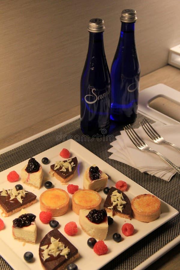 Delicioso y arsenal de la tentación de postres y de agua en botella de Saratoga en el hotel, Rochester, Nueva York, 2017 imagen de archivo libre de regalías