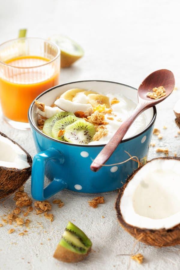 Delicioso yogur de coco con granola y fruta servida en el fondo de la luz Alimentos veganos sanos fotos de archivo libres de regalías