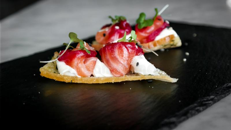 Delicious amuse bouche appetizer, cured salmon with beetroot, cheese and orange blossom - luxurious foods stock photo