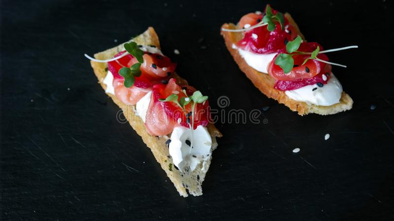 Delicious amuse bouche appetizer, cured salmon with beetroot, cheese and orange blossom - luxurious foods stock photography