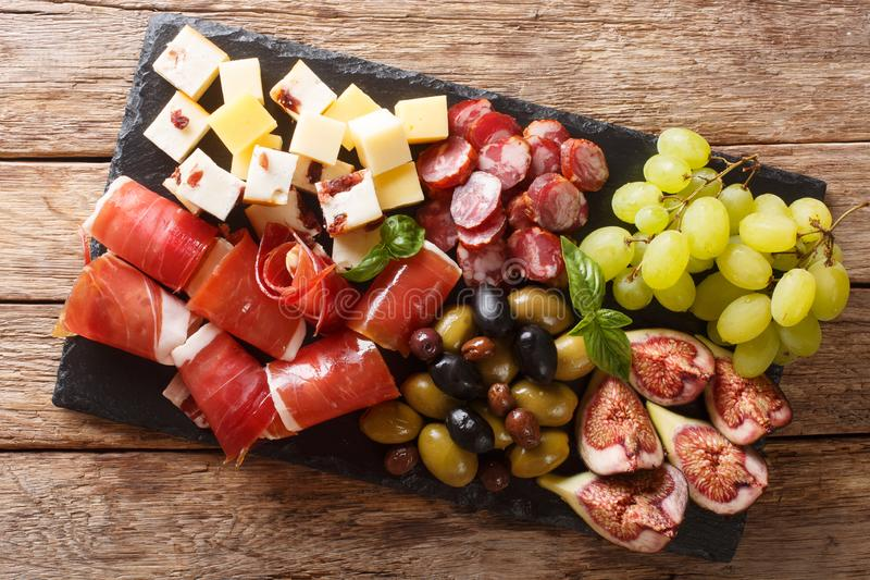 Delicious appetizer of antipasti from cheese, prosciutto ham, grapes, figs, sausages and olives close-up on a table. horizontal royalty free stock photography