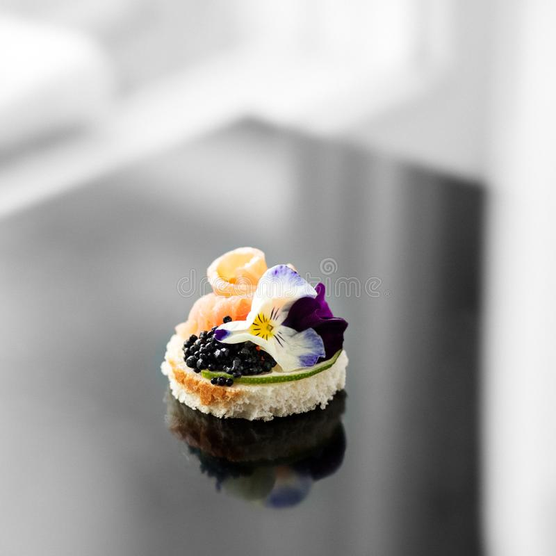 Delicious appetizer with fish and edible flowers. Concept for food, restaurant, menu, catering.  stock photo