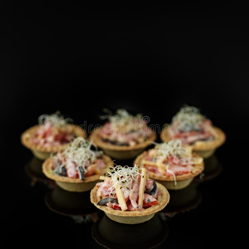 Delicious appetizer with ham, cheese, pepper and tomato in tartlets. Concept of food, restaurant, catering, menu.  stock photos