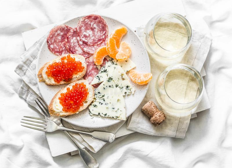 Delicious appetizer - red caviar sandwiches, blue cheese, salami, tangerines and white wine on a light background, top view. Flat lay royalty free stock photos