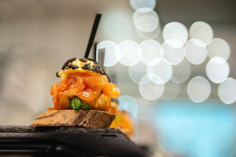Delicious appetizer with salmon. Closeup with bokeh. Delicious appetizer with salmon. Closeup with bokeh and glowing lights. Good catering service on event stock images