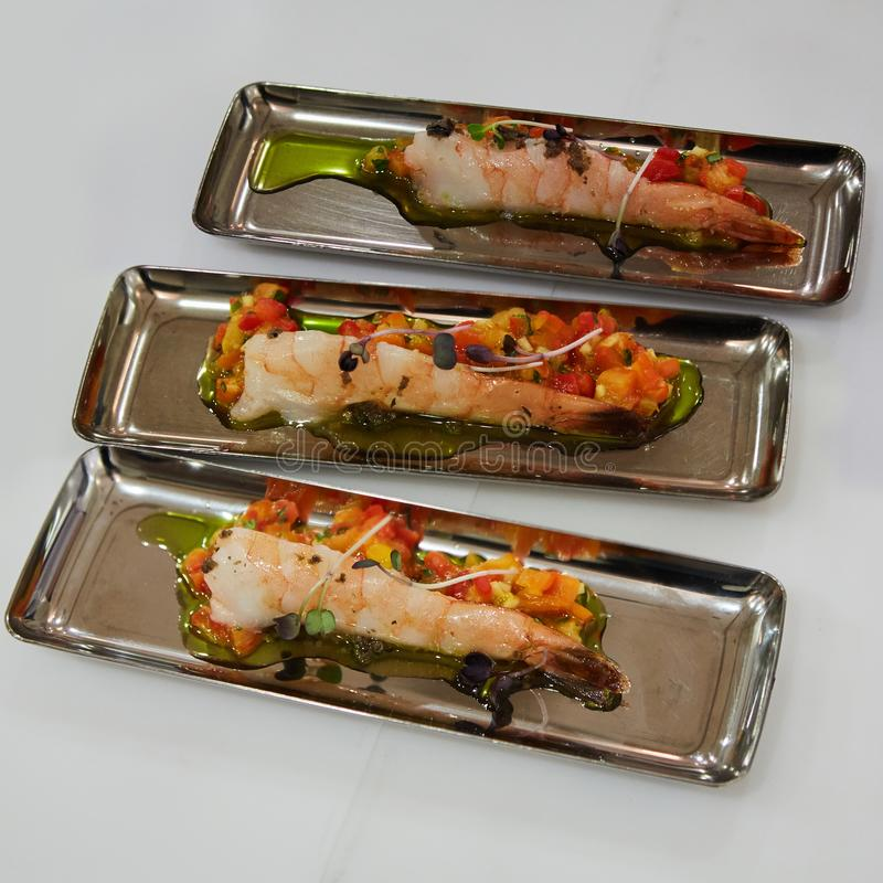 Delicious appetizer of shrimps with vegetables in chrome plates. stock photo