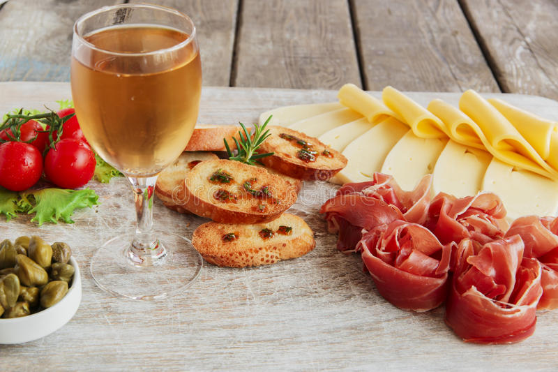 Delicious appetizer to wine - ham,prosciutto, cheese, capers, tomato, served on a light wooden board. Delicious appetizer to wine - ham,prosciutto, cheese stock image