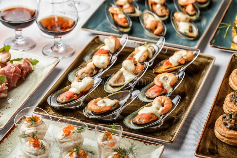 Delicious appetizers with mussels, shrimp and cheese sauce on banquet table. Gourmet food close up, snack, antipasti stock photography