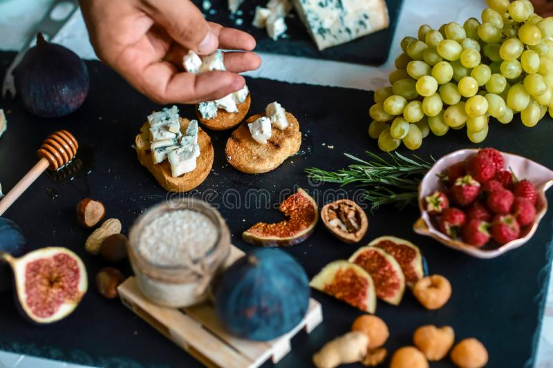 Delicious appetizers for wine or a snack - figs, Blue cheese and walnuts on cutting board. Food recipe concept stock photo